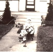 Image of My New Toys - Young child sitting in wagon with toys and a wooden floor train is along side on the sidewalk.