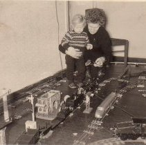 Image of Large Floor Layout from Germany. - Mother and Son enjoying a very large floor layout of O gauge & Standard Gauge trains. Visible are a Bing (Direction Board) 10/68 (7210) c. 1909-1929, a Bing 12/6160 18-volt triewagen (power car) c. 1932, a Marklin electric steeple cab CL 64/3020 c. 191901921, a Marklin 1955/0 depressed center flat car, a Marklin #13747 signal and a Marklin #435 central station. The steam locomotive and tender are unidentified.