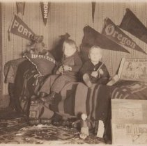 Image of Photo of Two Boys Sitting on Bed with Toy Train Set - Two boys on couch holding toy guns.  Flags hang behind them.  Bing O gauge clockwork toy train sits on circle of track in front of them.