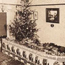 Image of Toy Train Layout under Christmas Tree - Photo of large elevated Christmas layout under tree.  Train appears to be 3-rail O gauge.