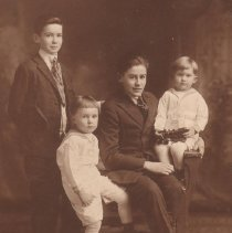 Image of Four Boys in Family with Toy Locomotive - Photograph of 4 boys in a family.  Youngest is holding a Kenton 2-4-0 locomotive which is used a photo prop.