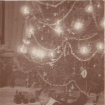Image of Czech Photo of Young Boy w. Toys at Christmas - Small boy lies under the Christmas tree, looking at toys.  Boat,  train, auto.  Train is a wooden pull toy.