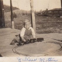 Image of Small Boy on Porch with Toy Train - Small photo of little boy sitting on porch with toy train on  circle of track.  Train is an American Flyer No. 0, type VI, O gauge clockwork locomotive (1916) with a #120, type II tender.  The cars are type VII, #1107 passenger car and #1108 baggage car.