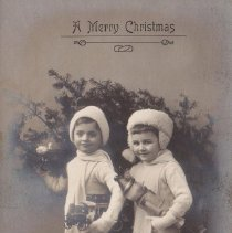 Image of A Merry Christmas - Two children holding a Bing clockwork auto-bus, circa 1910.