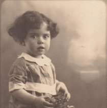 Image of It's MINE! - Small boy holding a Chein #270 trolley floor toy.