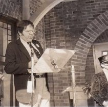 Image of TCA Museum Dedication. - Unidentified speaker with Ward Kimball in the background.