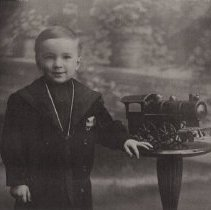 """Image of My Engine! - Young boy standing next to Pedestal holding a Schieble """"Hill Climber"""" friction toy locomotive. c. 1914-1916.  Note that the original image is much larger, the display image was cropped to show more detail."""