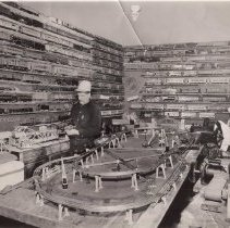 Image of Frank Rochat in His Toy Train Room - Frank Rochat in his toy train room. Shows elaborate layout and walls filled with toy trains. Lionel O and Standard gauge trains include #313 Bascule Bridge, c. 1940-42 and # 5 Special in standard gauge. O gauge layout has a milk car platform, crossing gates, highway signal, semaphore and street lamp.  Items identified by Jim Yocum.