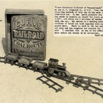 """Image of CURVE COAL ROUTE RAILROAD of PENNSYLVANIA - """"Curve Coal Route Railroad of Pennsylvania"""" Manufactured by C. C. Shepherd Co. of N.Y., circa 1860-1870. Track gauge is 1-3/4"""", there are eight sections of wooden track with metal rails and a working switch. Track sections are held together with notched splice bars. Paper labels are used only on the locomotive and box. Couplers are of a link and pin type. This set was part of the Ward Kimball collection which was sold in 2004 & 2005."""
