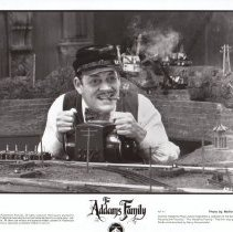 """Image of The Adams Family - Promotional Photograph for Paramount Pictures film """"The Adams Family"""" Shown in the Photograph is Gomez Adams ( Raul Julia) along with a Lionel ZW transformer, Lionel trackage and some 022 switches."""