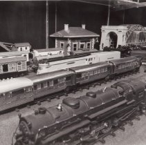 Image of Half a century of Toy Trains #2 - Lionel O gauge trains #700E scale Hudson, c. 1937-42; #616E Flying Yankee Diesel Power Car with # 617coach and #618 observation car, c. 1936-41; # 250E Hiawatha locomotive & # 250W tender, c. 1935-41; 800 series freight cars, # 813 cattle car, # 815 oil car, # 817 caboose, #816 hopper car, # 814 box car, # 814 refrigerator car, # 812 gondola car and # 810 crane car and a # 165 magnetic crane. In the rear are a Standard gauge # 124 City Station and a # 300 Hellgate Bridge.  Items identified by Jim Yocum.