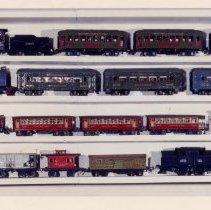 Image of Prewar train collection - Display shelf of O gauge prewar trains from the Charlie Weber collection.  Top Shelf:  Lionel / Ives #257 steam locomotive, 2 - # 610 Pullmans & # 612 observation car. (1931-1932)  Second from top shelf:  Ives # 3257R electric locomotive, 2 - # 141 parlor cars & # 142 observation car.   Third shelf from top:  Ives #1651 electric locomotive, 2 - # 1690 Pullmans, # 1691 observation car. (1932) & a # 3252 electric locomotive.  (1919-1927)  Bottom shelf:  Dorfan # 603 box car, # 605 coal hopper, # 606 caboose, Lionel Ives # 1678 stock car (1932), Ives #3255 electric locomotive (1925) & Ives electric locomotive # 3254 (1925).  Photo research by Jim Yocum.