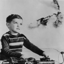 Image of Just like the real one. - Photograph of a young boy playing with Lionel trains with a real train shown in the background, as in his imagination. May have been a Lionel advertising items but we have no proof of that.  Trains shown are O gauge pre-war Lionel 2-6-2 # 1666 locomotive (1938-42), automatic coal dump car # 3659 (1939-42) & caboose # 657 (1934-42).