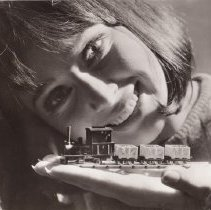 Image of Promotional photograph - Young girl holding a small scale train in the palm of her hand.  Train is made up of a tank locomotive and three coal cars.  The tank locomotive is Egger-Bahn # 102 and the three coal cars are Egger-Bahn # 2031 which included the coal load.  See more information on the scan of the photographs back.