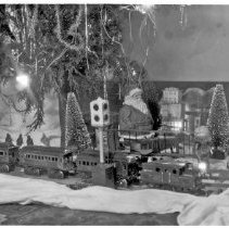 Image of Christmas Layout with Chair on Track - Christmas layout under tree.  Trains are mixed with Ives locomotive and Bing passenger cars made for the US market, also seen is a Lionel block signal.  The locomotive is an Ives #3253(B) electric profile loco, c. 1921-25 and Bing passenger cars # 528/31 combine, c. 1912-28, # 528/30 passenger car, c. 1912-28 & #528/36 observation car, c. 1912-28.  A # 078 Lionel block signal, c. 1924-32.