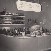 Image of Kaufmann's Display Window. - Photograph of Kaufmann's display window with standard gauge trains, Lionel except as noted. Top shelf:  # 402 electric locomotive, # 513 cattle car, # 219 crane car, #212 gondola & # 214 box car.  Center shelf:  #6 steam locomotive with NYC HRRR gold stamped on tender, # 116 ballast car, # 112 gondola, # 15 oil car & # 114box car.  Bottom shelf:  # 400E locomotive with Vanderbuilt tender, # 421 Westphal & # 420 Faye Passenger cars.  Layout:  Standard gauge # 53 Electric locomotive, # 35 Pullman, # 36 observation car.  A # 18 Pullman is seen in the rear.  Also shown are an Ives Grand Central Station & # 109 double arm signal and Lionel # 61 lamp post & # 89 flag pole.  Detailed research by Jim Yocum.