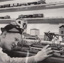 Image of George Whittaker checks out the trains. - Department Store train display showing American Flyer S gauge trains. A New Haven electric locomotive #499, A Seaboard Coaler #752, a log loader #960 and an American Flyer Lines Combine. See more information on the photos back scan.