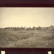 Image of P25763 - Hales & Symon's Team - Sepia tone print mounted on heavy embossed board, depicting a long line team hauling heavy machinery up to the Shawmut mine. 28-Mule team. Telephone or telegraph lines are along the road, the scenery is stark, with little vegetation.