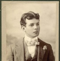 Image of P26953 - A black and white portrait of Billy Nelson. Wearing a 3-piece suit, shirt, plaid bow tie. Has flower on suit lapel. Hair is wavy with middle part.
