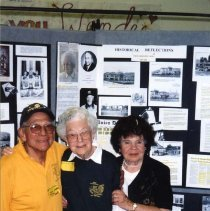 Image of P27701 - Centennial Celebration - Eleanor. McAllister Golly (class of 1918), Frank Borrengo, and Agnes Scott Rosasco in the Sonora High Library  standing in front of the historical displays, arm in arm, smiling.
