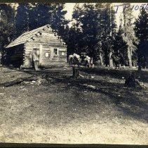 Image of TP1056 - Landscape - Cabin in the woods. With one man on a horse, one pack horse, a dog and 2 other men.
