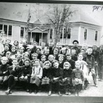 Image of TP1146 - Group - School, Summerville class. 1880 - 1900. They are sitting or standing outside in front of the school building. The teachers are standing in the back, one on the left and the other on the right. Two trees are behind the class and are in front of the building.