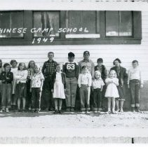 Image of TP1148 - Group - Chinese Camp School class of 1949. Students of various ages. Standing outside alone the side of the school building.
