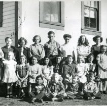 Image of TP1150 - Group - School - Chinese Camp - Circa 1950's. Students of various ages. They are standing at the back of the school. The teacher is on the left.