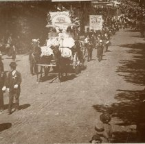 Image of TP1175 -  Admission Day Parade, September 9, 1895. In front there's a group of men walking down the street. Next is a N.D.G.W. float on a flat wagon driven by a lady and there are 2 other ladies have parcels. The horses are decorated, along with the float that has that has flowers on the float and a banner on the back. Next is a band marching down the street. And another group of men walking down the street, they have ribbons across there chest and the one in front are carrying a banner that says - N.S.G.W.. Following them is a float from the Salvation Army float. There are people standing on both sides of the street watching the parade.