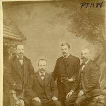 Image of TP1188 - Group - Unidentified men. There are 4 men. 2 are standing behind benches in dark suits with vests and bow ties. One of the standing men has a watch chain in vest. They both have mustache and hand in there front pockets. 2 men are sitting on benches. With dark suits , vest and bow ties. They have there hands on their legs and mustache.