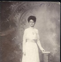 Image of TP1271 - Portrait - Unidentified lady. Studio setting, standing in front on an arch that's on the wall, with a book table that has a book on it. She is wearing a long white dress with long lace sleeves, a high collar and a locket hanging on the front of the dress. She has one hand resting on the book.