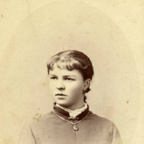 Image of TP1273 - Portrait - Unidentified girl. Studio scene, of an upper body photo. Wearing a dark outfit. has a chain with a locket around her neck, with a claps on the collar. Hair is pulled back and is wearing earrings.