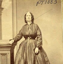Image of TP1383 - Unidentified woman, full length portrait. She is standing next to wooden column with her right hand resting on the column, wearing a dark colored dress with no collar, long sleeves from dropped shoulder, belted at natural waistline, probably over hoop, no bustle, hair is center parted and curls falling over ears she appears to be wearing a cap or hair decoration.