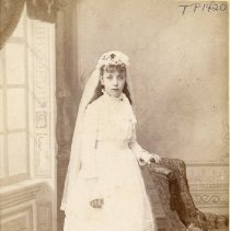 Image of TP1420 - Unidentified young woman, cabinet card full length photo, she is wearing light colored knee length dress, long sleeves, high collar bodice is bloused over natural waist belt, skirt is gathered into the bodice and finished with multiple rows of  tucks and a lace trim at the hem, she is wearing white tights, high buttoned shoes and fingerless gloves, also floral, lace and ribbon head dress with long veil, her hair is pulled back behind her ears and falls lose down her back, she has full bangs. She is pictured standing behind an upholstered chair in front of studio backdrop picture window.