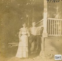 Image of TP1461 - Howes, Anna and Charles, photographed in front of their home, Charles is leaning with one arm resting on the porch railing, one leg bent at the knee, he is dressed casually in trousers and shirt with suspenders, he is clean shaven. Anna standing on his right dressed in summer white with a ruffle around the yoke of her dress and at the 3/4 length sleeves, two tiers of ruffles form the bottom of her floor length dress, all of the ruffles have decorative ribbon trim. Her hair is center parted and drawn back over her ears. They are standing under a tree in front of the railed and raised porch.