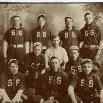 Image of TP1583 - Group - Baseball Team. Not identified. Could be either an Sonora or Soulsbyville team. Ten men and one dog. The coach is sitting in the middle of the group. Four men are standing in the back row. Middle row has three men. Front row has 3 men sitting on the floor with the dog. A catchers glove and mask is in front of the men in the first row. The uniforms are cleated shoes, knee high striped socks, dark pants with a belt, dark shirt that has the letters S S on the front and a ball cap.