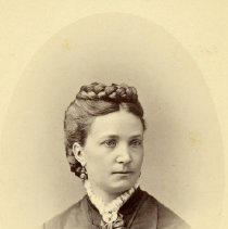 Image of TP1617 - Unidentified women.  Her hair is parted on the side and a braid is on the top of her head.  Lace is at the neckline of her dress.