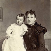 Image of TP1638 - Portrait-Mother & baby-not identified. The baby is wearing a long dress with long sleeves.  The mother is wearing a dress with long sleeves, lace at the cuffs and is puffy at the shoulder.  Her hair is parted in the center, pulled back and the bangs are curly.