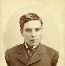 Image of TP1639 - Portrait-Unidentified young man.  He is wearing a suit jacket with a large tie.  A pin is seen on the tie.  His hair is parted on the side.