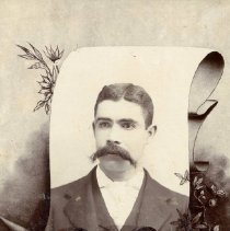 Image of TP1645 - Unidentified man.  The photo is on a scroll frame.  He is wearing a suit, vest, dress shirt and tie.  He has a full mustache.  His hair is parted on the side.