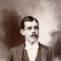 Image of TP1653 - Unidentifed man.  He is wearing a suit with vest, dress shirt and bow tie.  A watch fob can be seen.  He has a mustache and his hair is parted on the side.