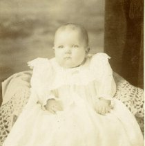 Image of TP1655 - Unidentified baby sitting in a chair.  The baby is wearing a long dress with long sleeves.  Eyelet is on the hem of the skirt.
