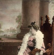 Image of TP1659 - Unidentified women sitting in a chair.  The photo is tinted in pink.  She is sitting in a large ornate chair.  Her pink dress is long with long sleeves.  Three stripes are at the edge of the hem.  A large feather boa is around her neck and shoulders. Her hair is rolled on the sides and pulled back.  A bow is on the top of her head.