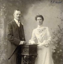 Image of TP1660 - Wedding portrait of and unidentified couple. They are standing next to a pedestal. He is wearing a suit with a tail and dress shirt and tie. She is wearing a wedding dress with long sleeves. A tiara is on her head. Her hair is pulled back.