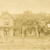 Image of TP1669 - Building-House-not identified.  Circa 1850 - 1890.  Sepia toned photograph.  Unidentified location.  A wrap around porch surrounds the two story home which has gingerbread trim.  Trees are in the front yard.  An unidentified man and women are standing in the front yard.