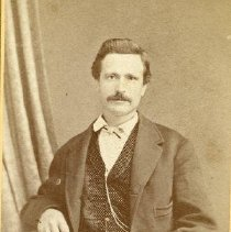 Image of TP1697 - Dressed in frock coat, vest,  watch on silver chain.  He has a mustache and his hair is parted on the side.