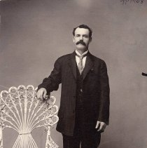 Image of TP1708 - Studio portrait of unidentified man. Man with mustache is dressed in dark pants, jacket, and vest with white shirt and a tie. His right arm resting on fan-shaped back of wicker chair