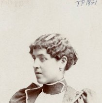Image of TP1821 - Portrait-Woman not identified. Young woman with dark wavy hair, dress is with puffy sleeves with wide lapels, and wide dark neck choker. catalog records does not match photo