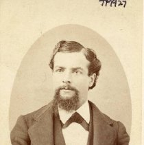 Image of TP1927 - Unidentified man, . Circa 1860 - 1900, Bacigalupi Family Album. He is pictured wearing wide lapel coat over a darker vest with rolled lapel. The vest is unbuttoned over a white shirt, spread collar with ribbon tie.  There is a watch fob chain in the upper vest buttonhole.  His hair is thick and wavy, parted on left and combed to the right, worn long over the ears.  He has a small moustache over untrimmed van dyke or blunt trimmed chin beard.