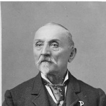 Image of TP203 - Photo of Louis August Haagan, music teacher. Older gentleman dressed in dark three-piece suit. Tweed jacket with the letter P on the left shoulder above the pocket, watch chain going through a button hole in the vest, large knotted tie. He has a small goatee and a full moustache. Back states, Born in Prussia 1824. Naturalized Oct. 20, 1861 in Tuolumne County. Registered to vote in 1867.